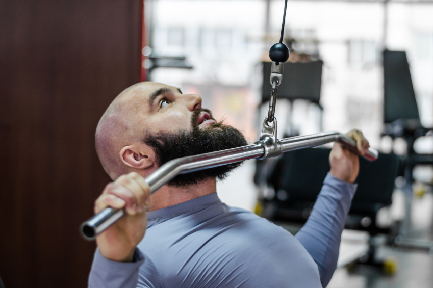 Male athlete doing exercises on pulldown machine in the gym