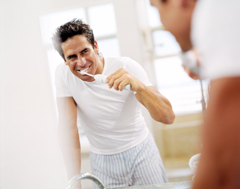 Man teeth brushing with electric toothbrush