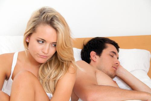 wpid woman sitting bed upset while man sleeping